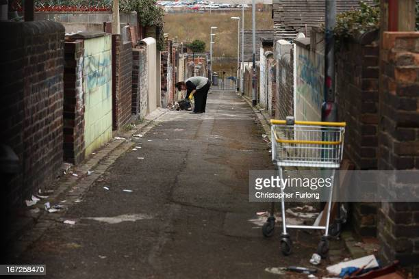 A woman performs maintainence work on her home next to derelict houses in the Cobridge area of StokeOnTrent that are being sold by the council for...