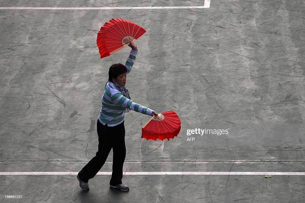 A woman performs tai chi with fans in Hong Kong on December 24, 2012. Different forms of tai chi excercise untilize the fan, with some being performed slowly and softly, but some include vigorous and fast movements ending with a loud snap of the closing and opening of the fan. AFP PHOTO / Dale de la Rey
