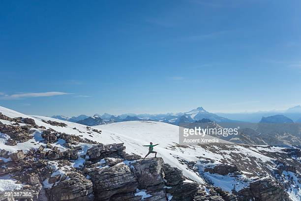 Woman performs yoga move on mountain summit
