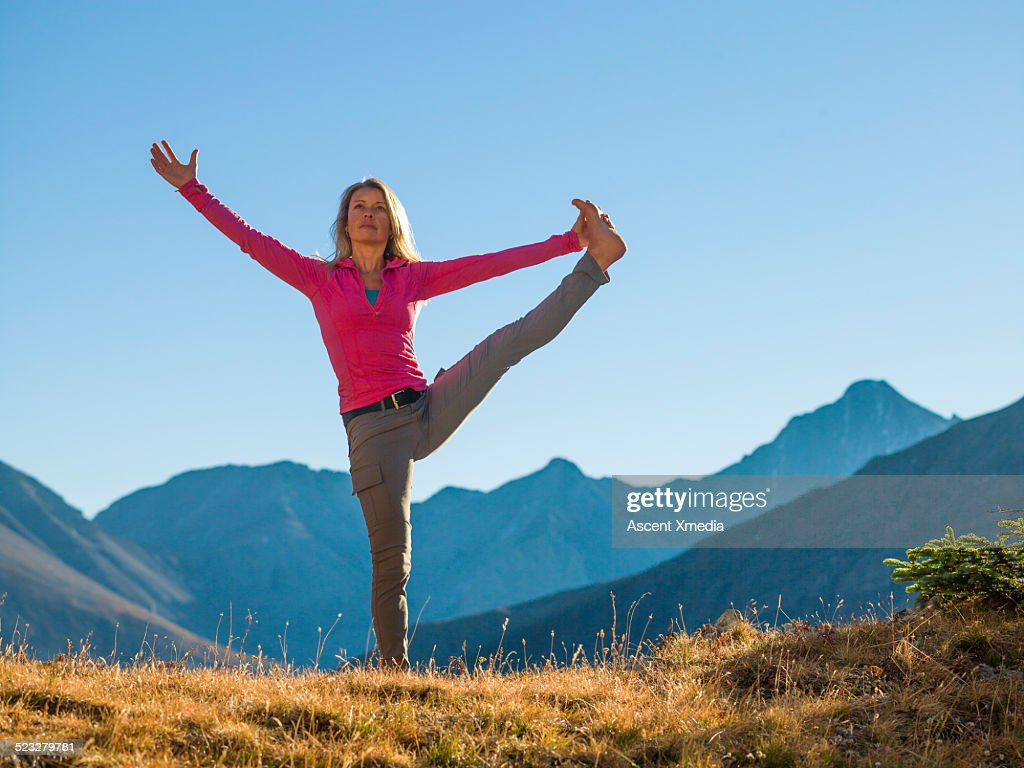 Woman performs yoga position in mountain meadow