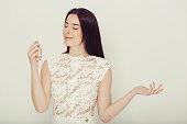 Woman perfume portrait in white dress female model aroma smell. Studio shot.