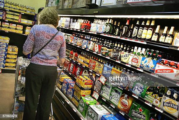 A woman peruses the beer cooler display in a grocery store May 9 2006 in Des Plaines Illinois With new flavors and packaging beer sales reportedly...