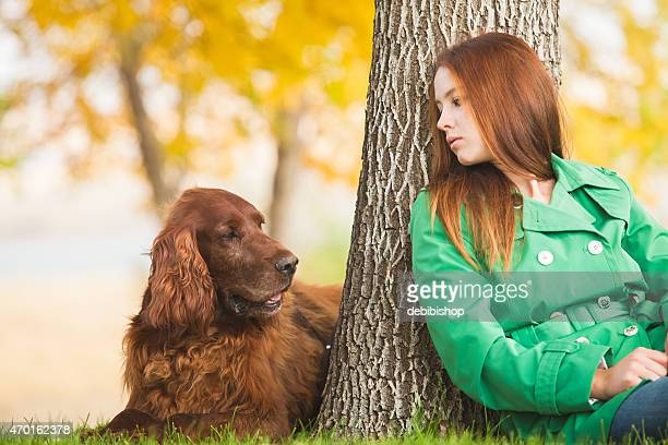 Woman & pet dog sitting and relaxing together outdoors