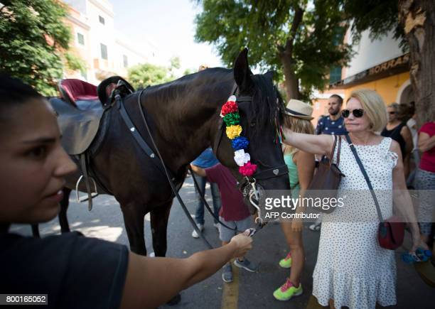 A woman pets a horse during the traditional San Juan festival in the town of Ciutadella on the Balearic Island of Menorca on the eve of Saint John's...