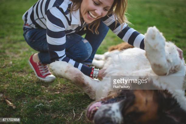 Woman petting a dog on a lawn