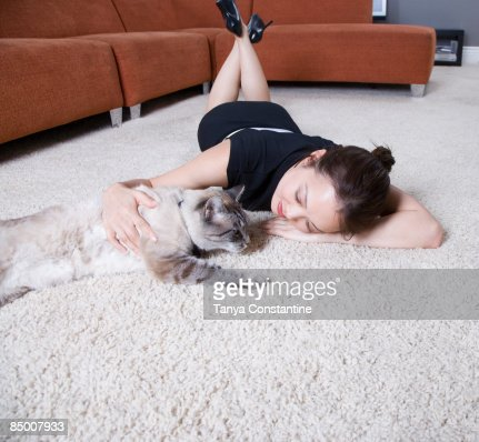 Woman petting cat on floor : Foto de stock