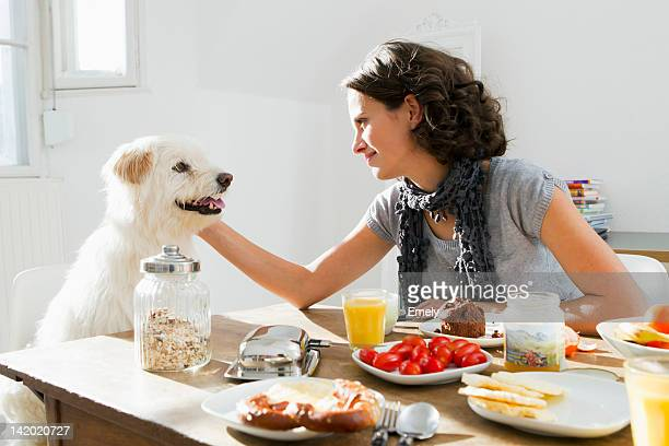 Woman petting dog at table