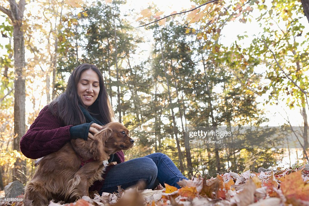 Woman petting her dog in a park : Stock Photo
