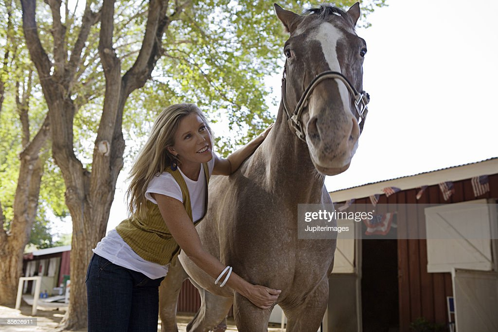Woman petting horse : Stock Photo