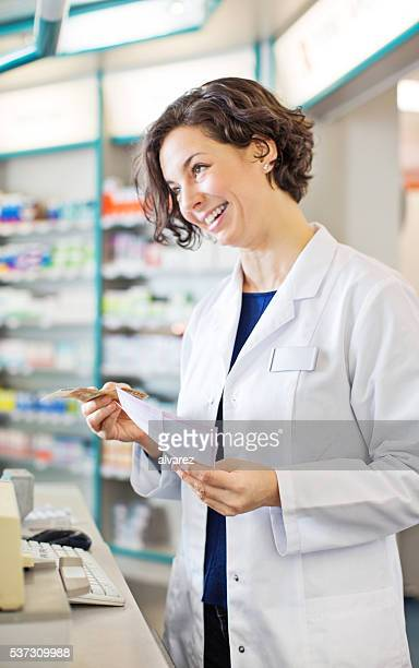 Femme pharmacien collecte de l'argent de client