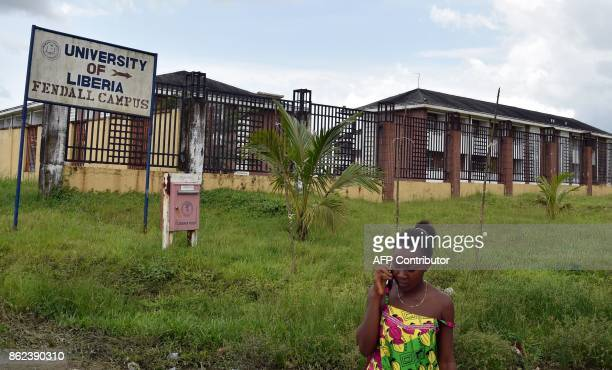 A woman phones outside the Fendall Campus of the University of Liberia near Monrovia on October 12 2017 / AFP PHOTO / ISSOUF SANOGO