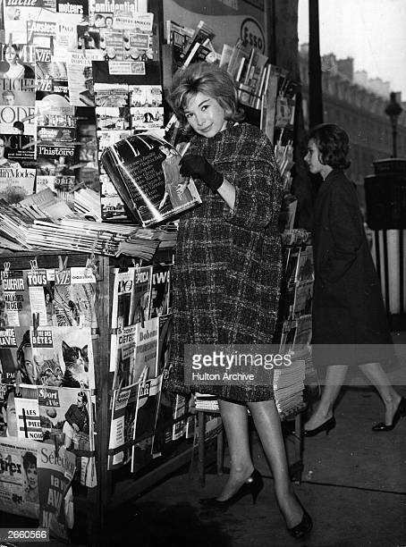 A woman photographed reading the French fashion magazine 'Elle' at a Paris newsstand