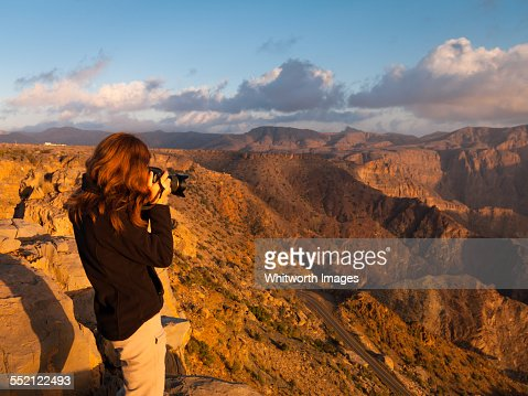 Woman photographer at sunset in Oman mountains