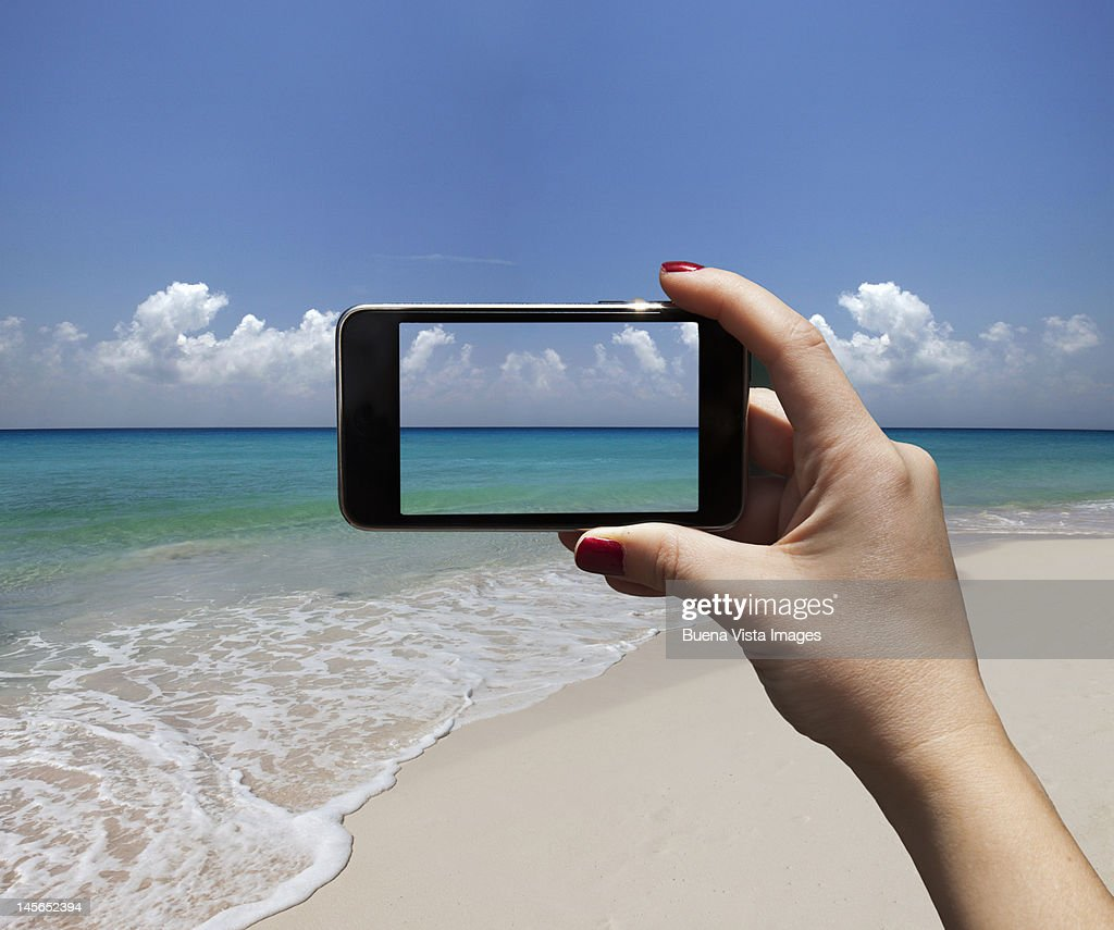 woman photographing a beach with i-phone : Stock Photo