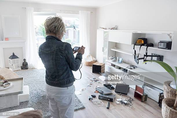 Woman photographing chaos after burglary when coming back in her one-family house