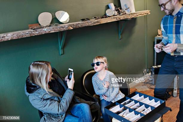 Woman photographing daughter wearing eyeglasses in workshop while father looking at him