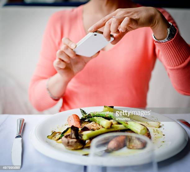Woman photographing food with mobile phone