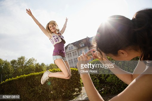 Woman photographing friend jumping : Stock Photo