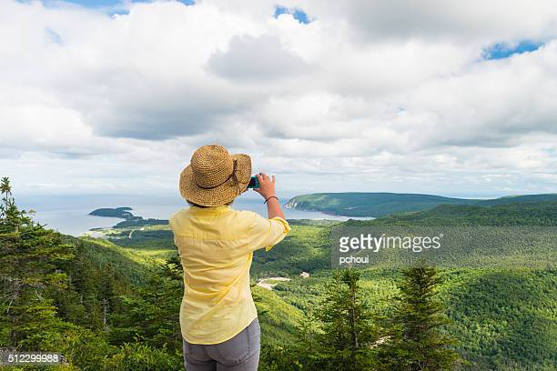 Woman photographing landscape, Cabot trail, Cape Breton, Nova Scotia