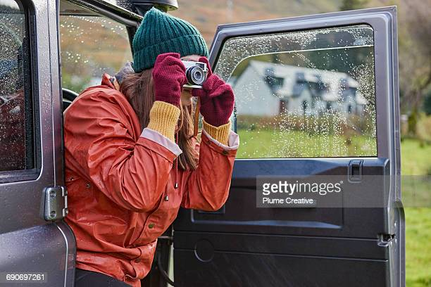 Woman photographing landscape from car