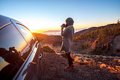 Woman photographing beautiful landscape above the clouds near the car on the sunset