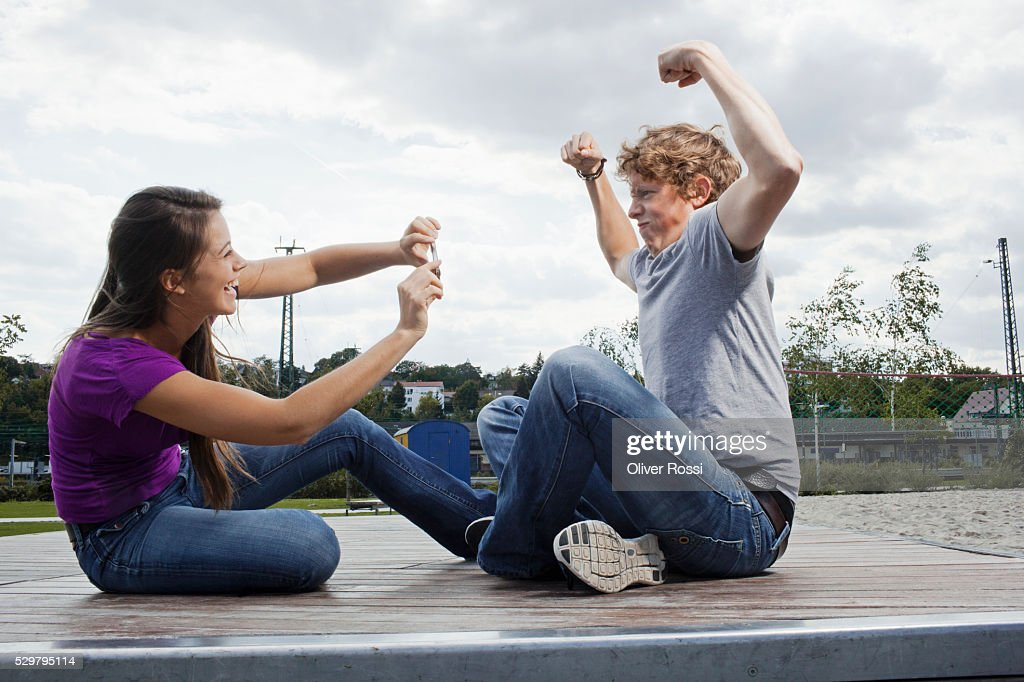 Woman photographing man flexing muscles : Stockfoto