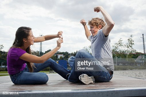 Woman photographing man flexing muscles : Foto stock