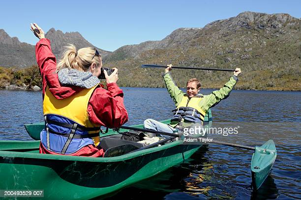 Woman photographing man in canoe