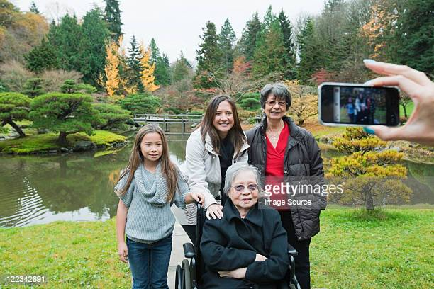 Woman photographing multi generation family
