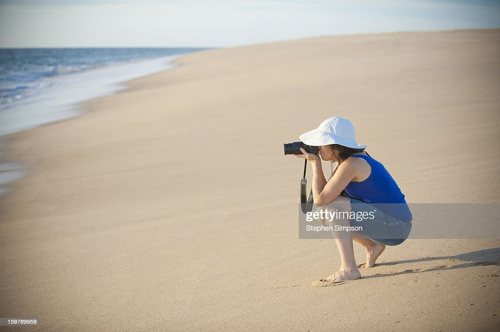 woman photographing on pristine empty beach : Stock Photo
