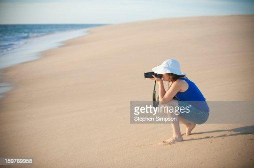 woman photographing on pristine empty beach : Stock Photo
