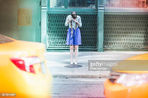 Woman photographing on street, New York, US