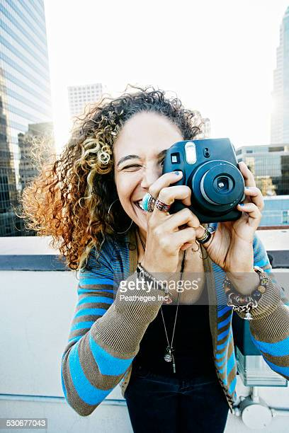 Woman photographing on urban rooftop