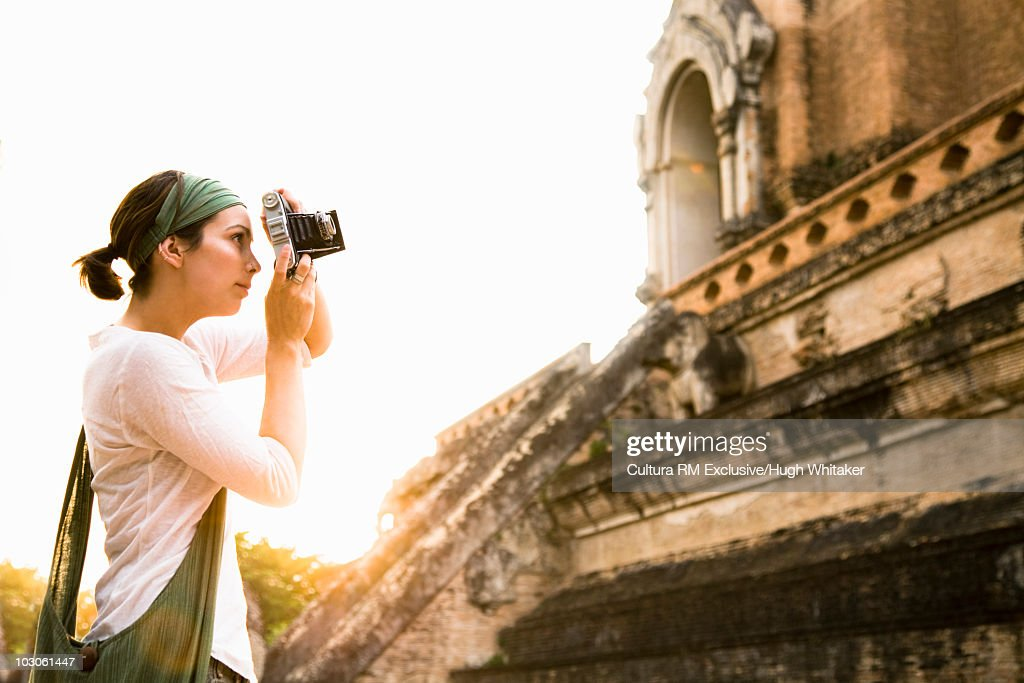 Woman photographing temple : Stock Photo