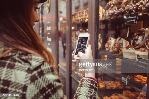 Woman photographing the candy shop window