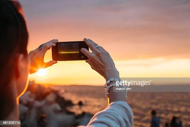 Mulher fotografando ao pôr do sol