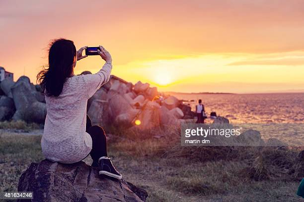 Woman photographing the sunset