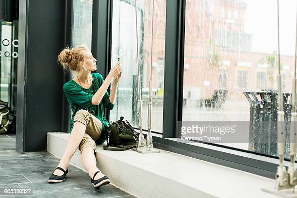 Woman photographing through glass while sitting on sill