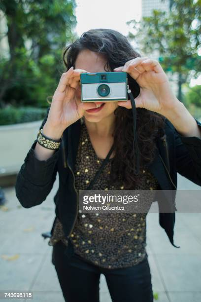 Woman photographing through vintage camera