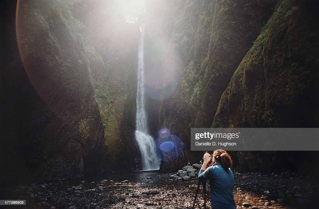 Woman photographing waterfall in gorge