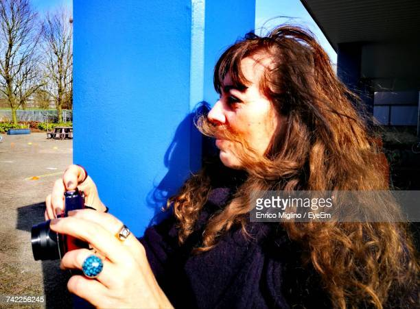 Woman Photographing With Camera By Pillar On Sunny Day