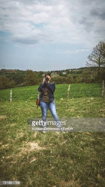 Woman Photographing With Camera While Standing On Grassy Field Against Sky