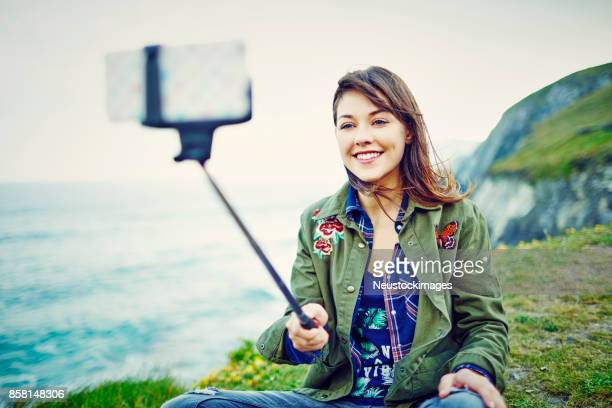 Woman photographing with smart phone fixed to monopod on cliff