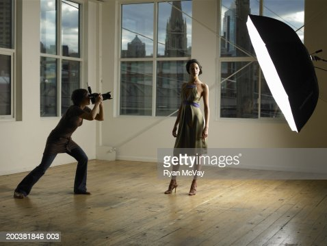 Woman photographing young female model in photo studio, dusk