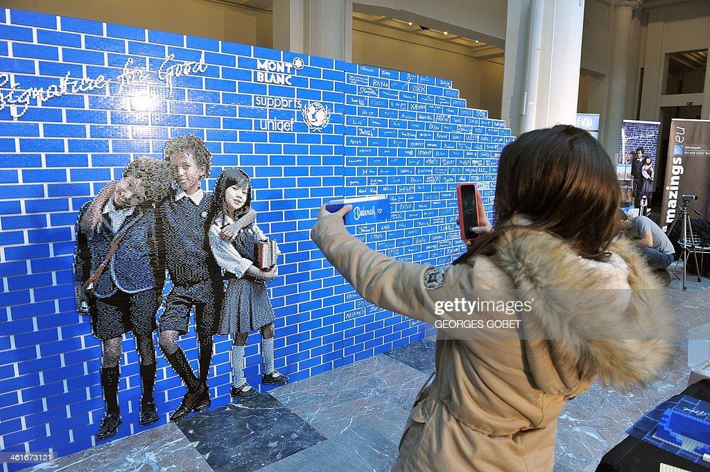 A woman photographs a brick made of Lego blocks in front of a Lego wall as pupils and volunteers attempt to build the world's longest Lego wall at the Palais des Beaux-Arts in Brussels (BOZAR) on January 10, 2014. The event takes place until January 11 to support a UNICEF campaign to raise awareness about the need to construct new schools in developing countries.