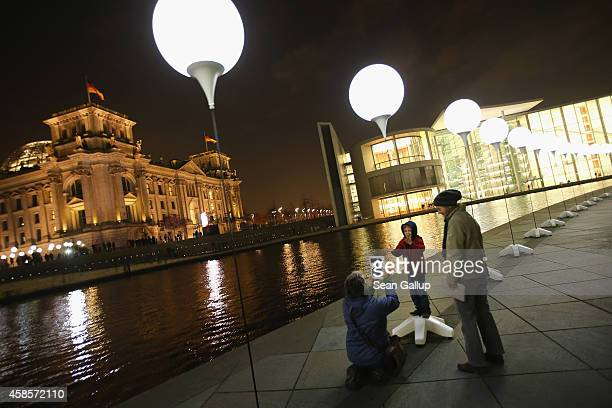 A woman photographs a child with a tablet computer at a light installation of balloons tethered to lamps illuminating the course of the Berlin Wall...