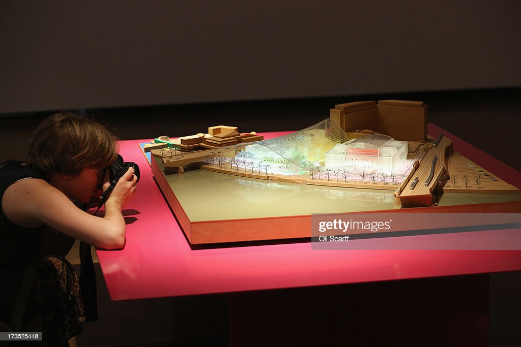 A woman photographs a model of the proposed development for London's Southbank Centre in the exhibition 'Richard Rogers