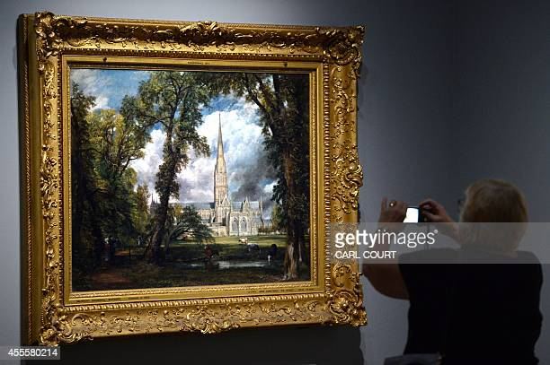 A woman photographs a painting by British artist John Constable entitled 'Salisbury Cathedral from the Bishops Grounds' during a photocall at the...