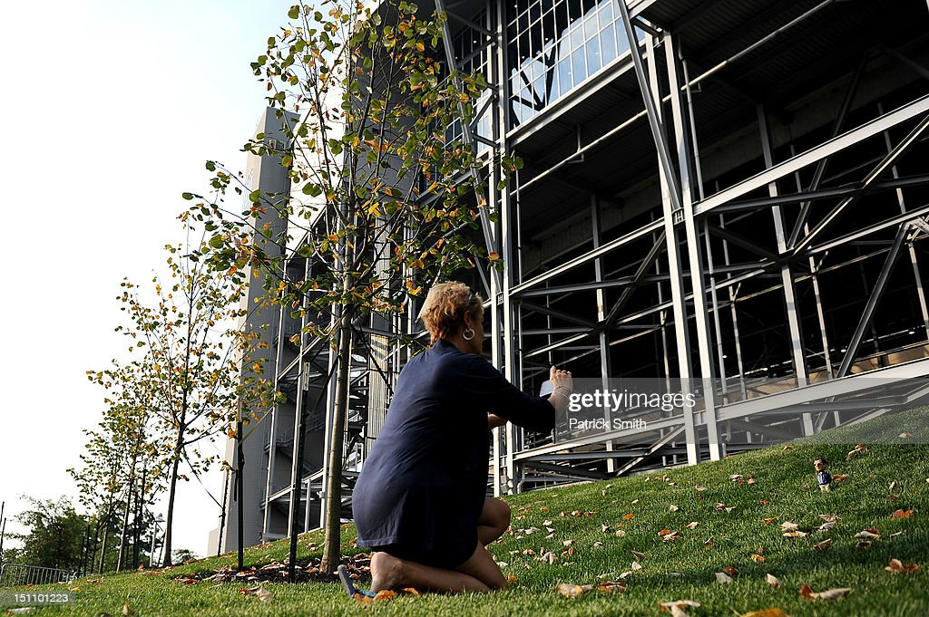 A woman photographs a toy of a former Penn State football coach Joe Paterno at the former site of the Joe Paterno statue prior to the Penn State playing the Ohio Bobcats at Beaver Stadium on September 1, 2012 in State College, Pennsylvania.