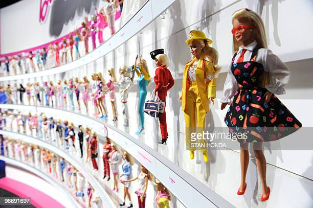 A woman photographs a wall of Barbie dolls in the Mattel display at the annual Toy Fair February 14 2010 in New York AFP PHOTO/Stan Honda